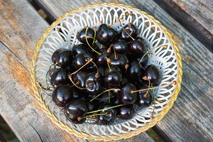 White plate of ripe black cherries
