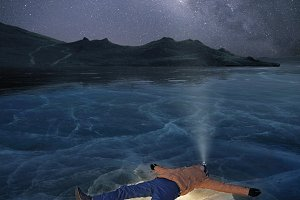 Man laying on a frozen lake.