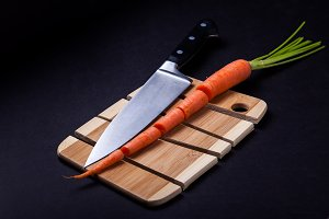 Knife with carrot and wooden cutting