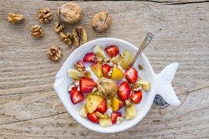 A bowl of fruit, walnuts and yogurt