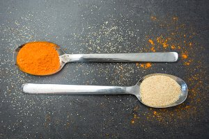 Spoons with spices on slate table