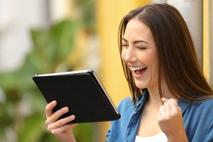 Excited woman checking news on table