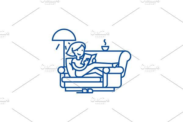 Woman at home at sofa reading book