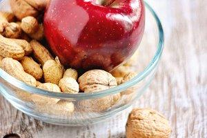 Walnuts, peanuts, and red apple