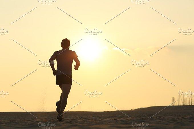Backlight of a jogger running on the beach.jpg - Sports