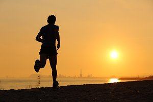 Backlight of a men running on the beach at sunset.jpg