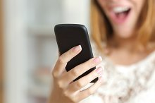 Close up of a surprised woman using a smart phone at home.jpg