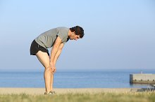 Exhausted runner man resting on the beach after workout.jpg