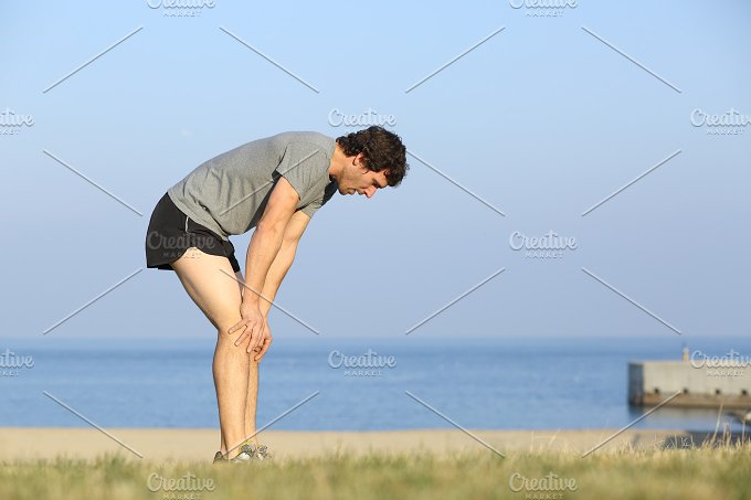 Exhausted runner man resting on the beach after workout.jpg - Sports