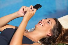 Girl texting on a smart phone on an hotel poolside on vacations.jpg