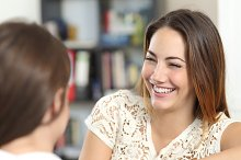 Happy woman talking and laughing with a friend at home.jpg