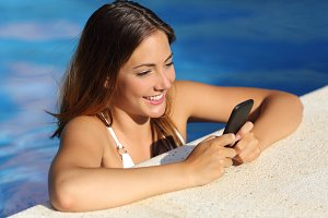 Happy girl using a smart phone in a swimming pool in summer vacations.jpg