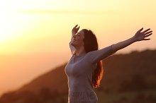 Woman at sunset breathing fresh air raising arms.jpg