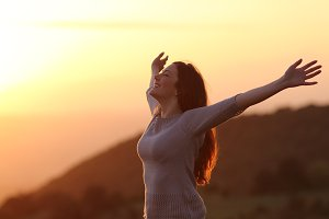 Woman at sunset breathing fresh air raising arms.jpg