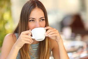 Woman drinking coffee from a cup in a restaurant terrace.jpg