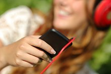 Woman hand using a smart phone to listen to the music with headphones.jpg