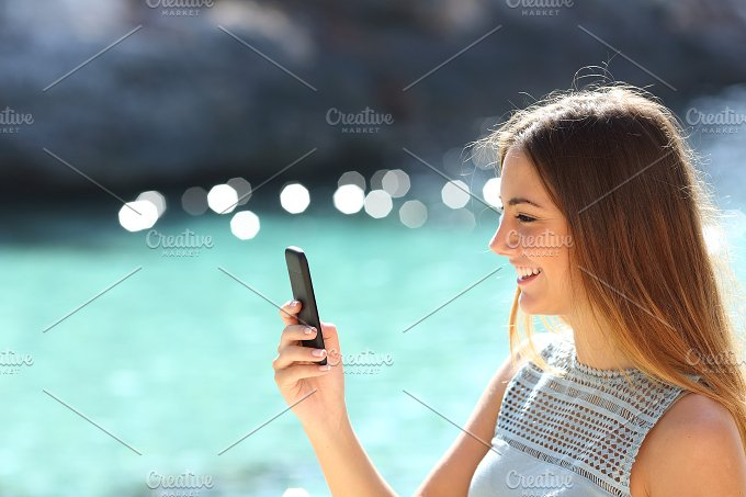 Woman using a smart phone in a tropical beach in vacations.jpg - Technology