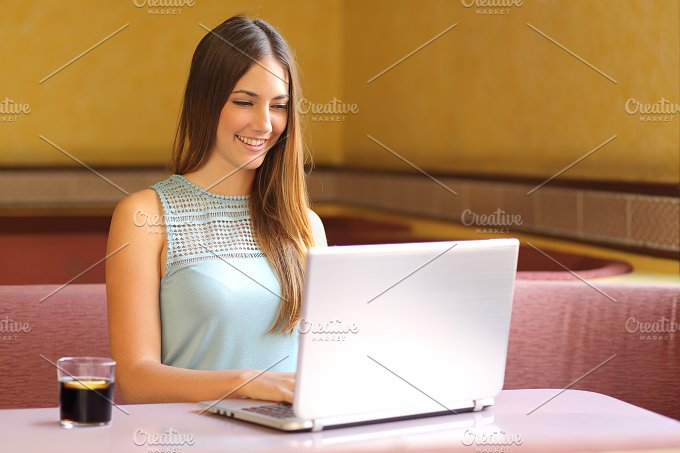 Girl working with a laptop in a restaurant.jpg - Technology
