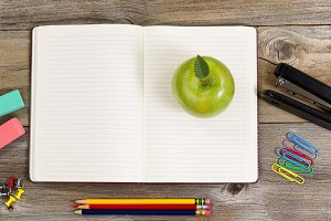 Notepad with supplies and apple