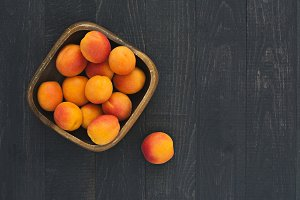 Apricots in a wooden, square dish.