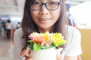 asia woman hold pot flower.