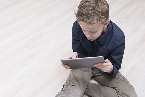 Kid with ipad on floor
