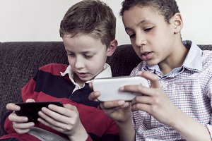 two kids playing on smartphone