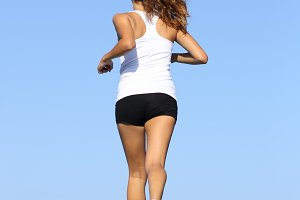 Back view of a fitness woman running on blue.jpg