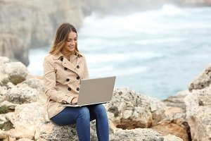 Beautiful woman browsing her laptop in winter on the coast.jpg