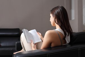 Beautiful woman reading a book sitting on a couch.jpg