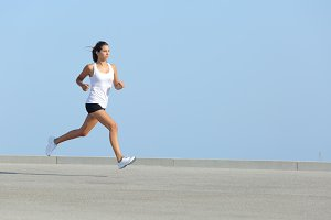 Beautiful woman running with the sky in the background.jpg