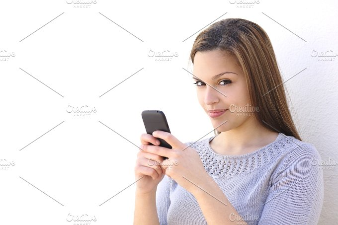 Beautiful woman texting on a smartphone and looking at camera.jpg - Technology