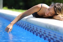 Casual happy woman playing with water in a swimming pool.jpg