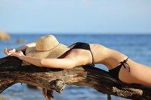 Fitness woman sunbathing on the beach sleeping.jpg