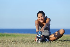 Fitness runner woman stretching on the grass.jpg