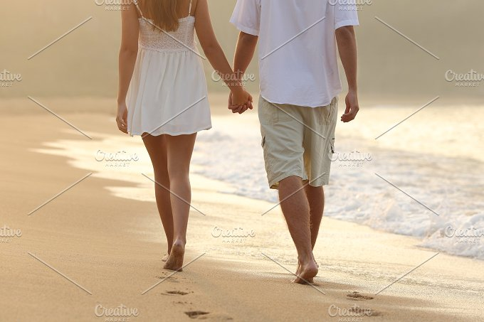 Couple taking a walk holding hands on the beach.jpg - People