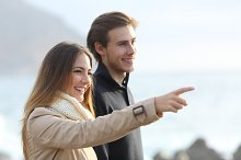 Couple looking forward on the beach and pointing.jpg