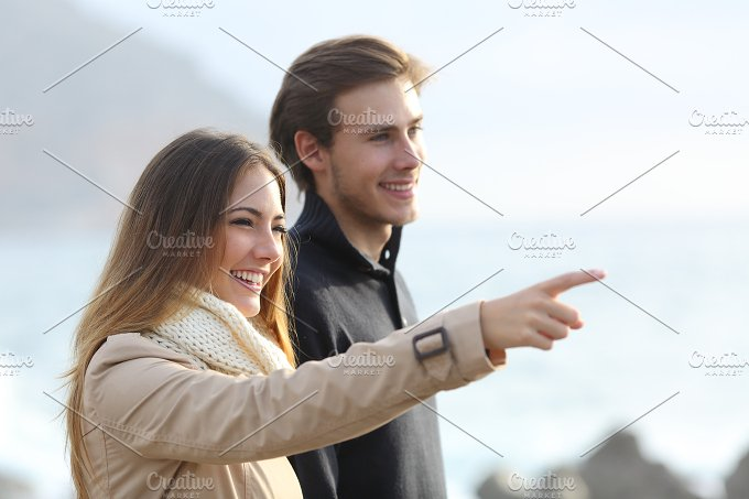 Couple looking forward on the beach and pointing.jpg - People