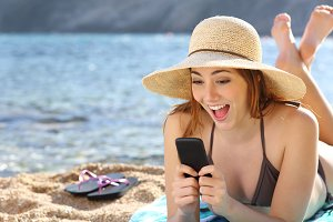 Funny surprised woman watching social media in a smart phone on the beach.jpg
