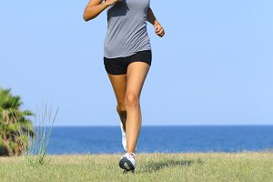 Front view of a beautiful woman running on the grass.jpg