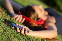 Girl listening music with headphones and holding a smart phone lying on the grass.jpg