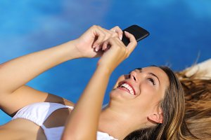 Funny woman using her smart phone in summer vacations.jpg