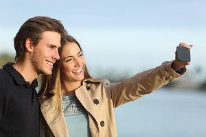 Happy couple photographing a selfie with the smart phone.jpg