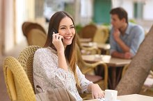 Happy woman calling on the phone in a restaurant.jpg