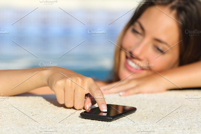 Happy woman in vacations texting in a smart phone bathing in a swimming pool.jpg - Technology