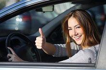Happy woman inside a car gesturing thumb up.jpg