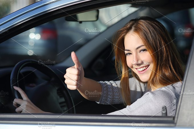Happy woman inside a car gesturing thumb up.jpg - Transportation