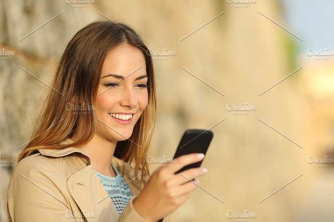 Happy woman using a smart phone in an old town.jpg - Technology