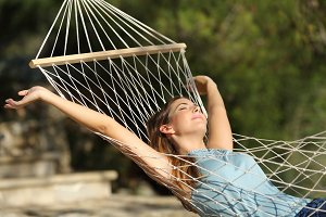 Happy woman relaxing on a hammock on holidays and raising arms.jpg