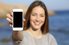 Happy woman showing a smart phone display on the beach.jpg